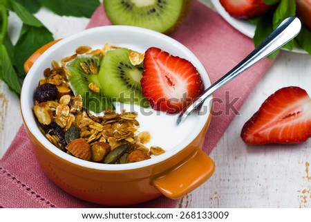 breakfast with  fresh Greek yogurt, strawberries, kiwi and granola on a white wooden table  - stock photo