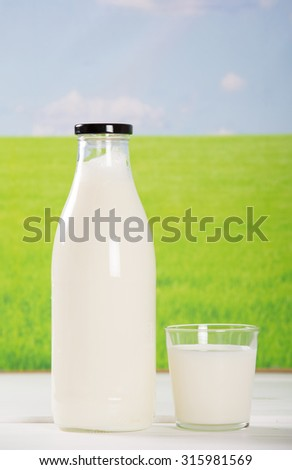 Breakfast with fresh milk by the field - stock photo