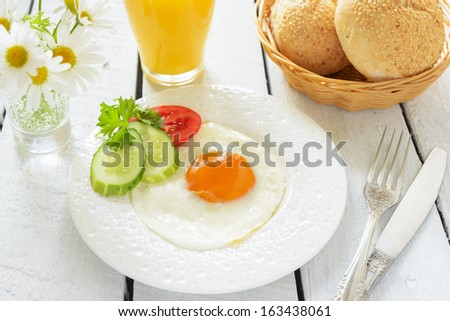 Breakfast with fried egg and orange juice - stock photo
