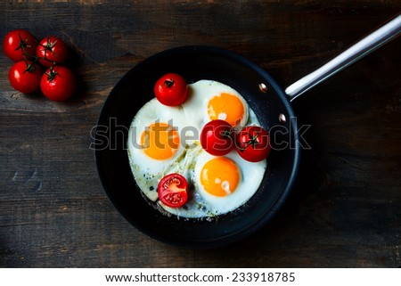 Breakfast with Fried eggs and fresh tomatoes on pan over rustic wooden texture, top view - stock photo