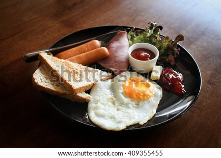 Breakfast with fried eggs, bacon and sausages. - stock photo