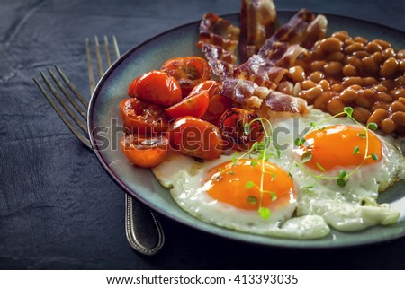 Breakfast with fried eggs, bacon, beans and cherry tomatoes   - stock photo