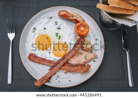 breakfast with fried eggs, bacon, sausages,toasts  - stock photo