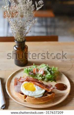 breakfast with fried eggs, bacon, sausages,waffle and fresh salad - stock photo