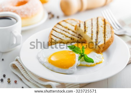 Breakfast with fried eggs, coffee and dessert on table. Healthy food