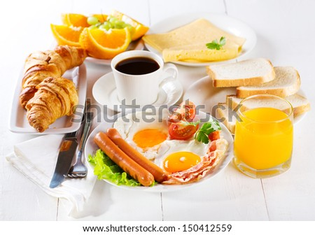 breakfast with fried eggs, croissants, juice, coffee and fruits - stock photo