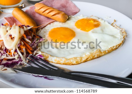 Breakfast with fried eggs, sausages, ham  and salad. - stock photo