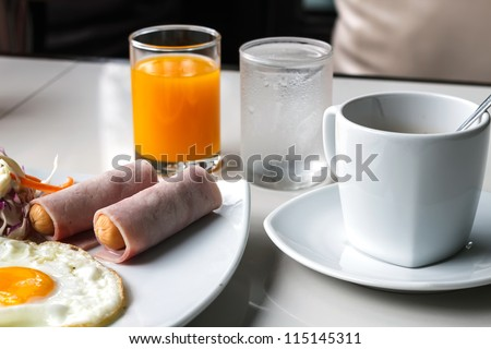 Breakfast with fried eggs, sausages, ham, juice  and coffee. - stock photo