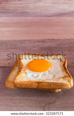 breakfast with fried eggs, toasts on wooden table.