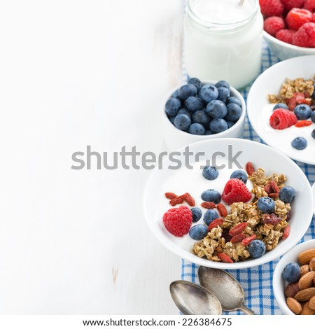 breakfast with granola, yogurt and berries on a white wooden table and space for text, top view - stock photo