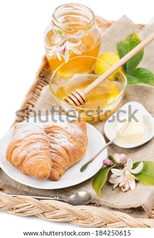 Breakfast with honey and fresh croissants on wicker tray, isolated on white - stock photo
