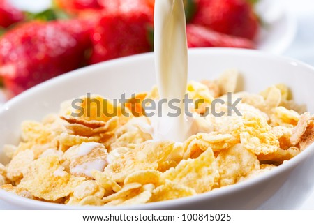 Breakfast with milk pouring in corn flakes - stock photo