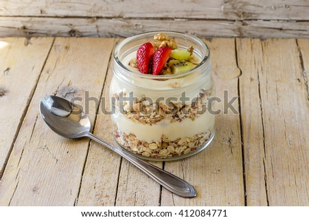 Breakfast with muslie. Healthy breakfast concept with oat flakes and fresh fruits and berries on wooden rustic background.