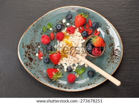 Breakfast with oatmeal, fresh berries and honey - stock photo