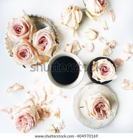 Breakfast with pink rose flower, petals, vintage plates, golden tray and black coffee mug composition. Flat lay, top view - stock photo