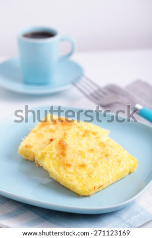 Breakfast with polenta and coffee. Selective focus on the top slice of polenta - stock photo