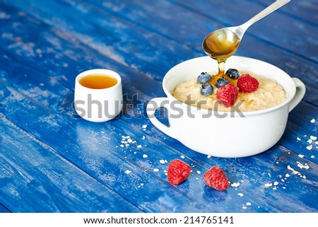 Breakfast with porridge and spoon poring honey, berries, on a blue wooden table - stock photo