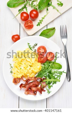 Breakfast with scrambled eggs, bacon and vegetables, top view - stock photo