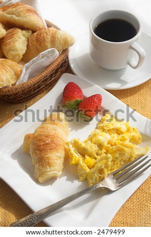 breakfast with scrambled eggs, croissants and coffee