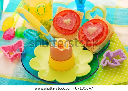 breakfast with soft boiled egg,juice  and sandwiches for child