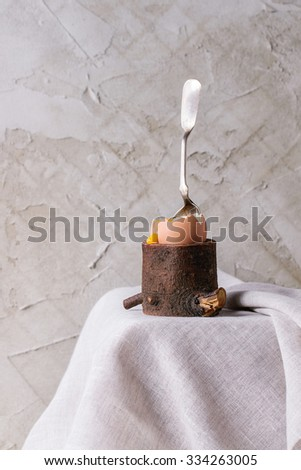Breakfast with started eating soft-boiled egg with pouring yolk in wooden eggcup with silver spoon on white cloth over white table. With plastered wall at background - stock photo