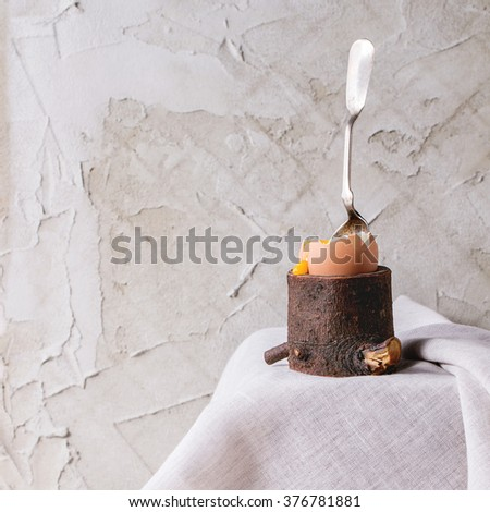 Breakfast with started eating soft-boiled egg with pouring yolk in wooden eggcup with silver spoon on white cloth over white table. With plastered wall at background. Square image - stock photo