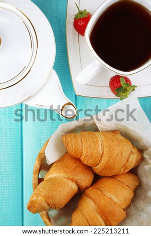 Breakfast with tea and fresh croissants on wooden table background - stock photo