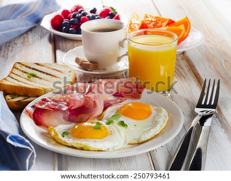 Breakfast with two fried eggs, bacon,toasts,orange  juice and coffee.Selective focus - stock photo