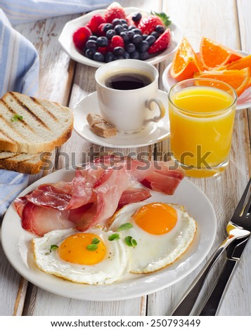 Breakfast with two fried eggs, bacon,toasts,orange  juice. Selective focus - stock photo