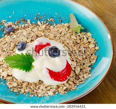 Breakfast with yogurt, berries and muesli. Selective focus - stock photo