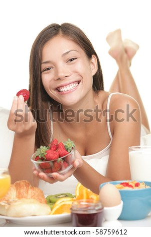 Breakfast. Young woman eating big breakfast in bed showing fresh strawberries smiling. Cute Asian / caucasian model with adorable smile isolated on white background. - stock photo
