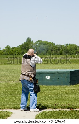breaking a clay pigeons at a trap shoot range - stock photo