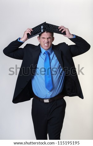 breaking a keyboard at work he must be having a bad day - stock photo