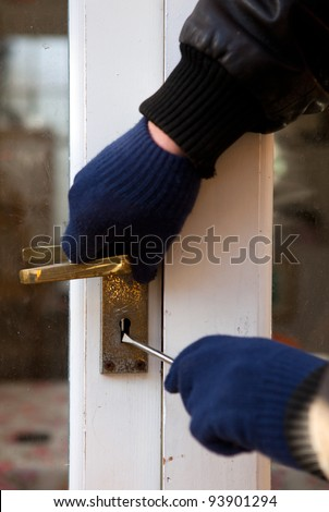 Breaking and entering home or house, Burglar with screwdriver force open door. Thief attempting to breach security