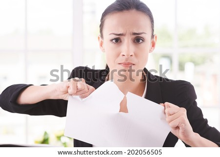 Breaking contract. Furious young woman in formalwear tearing up paper while sitting at the table