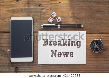 Breaking News Words written on white on wooden desk with dice,compass,smart phone and pen.Top view conceptual - stock photo