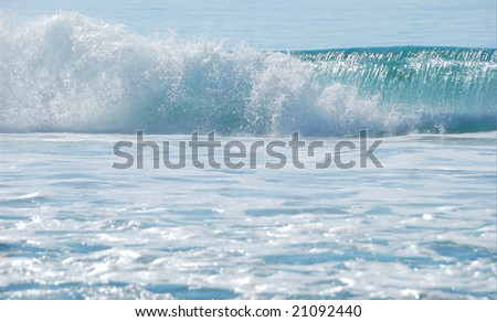 breaking ocean wave shown on a sunny day with foam in the foreground