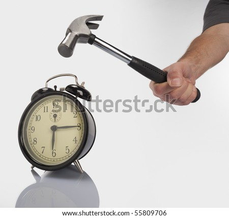 Breaking the alarm clock with a hammer - stock photo