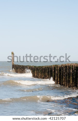 Breaking the waves at the beach with wooden poles - stock photo