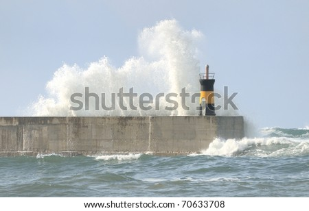 Breaking wave on lighthouse wall - stock photo