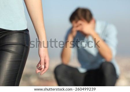 Breakup of a couple with a sad man in the background and the girlfriend leaving him in the foreground - stock photo