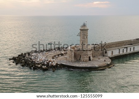 Breakwater and lighthouse in the port of Livorno; Italy. - stock photo