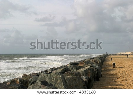 Breakwater - Massive stone structure to prevent erosion of sand dunes on the French Atlantic coast. - stock photo
