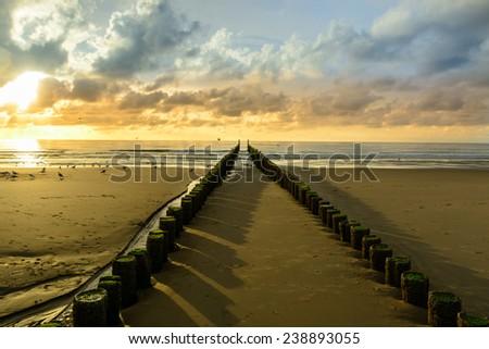 Breakwaters on the beach at sunset in Domburg, Zeeland,  Holland  - stock photo