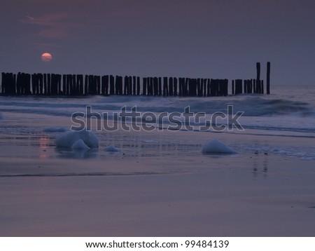 breakwaters on the beach of Cadzand i n the Netherlands - stock photo