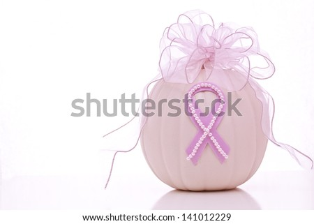 Breast Cancer Awareness ribbon on pink pumpkin, topped with pink ribbon bow - stock photo