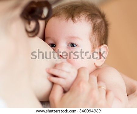 Breast feeding 3 months old baby boy - stock photo