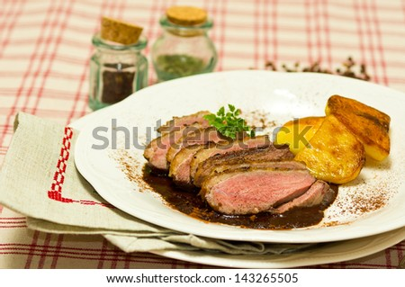 Breast of Duck (Magret de Canard) with cacao sauce and backed potatoes - stock photo