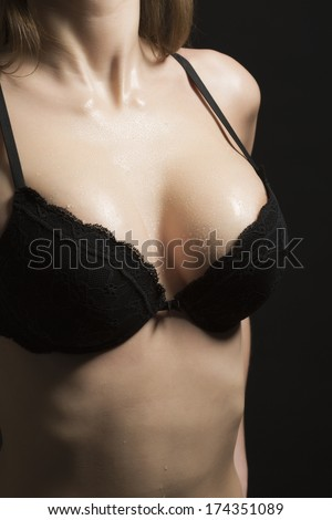 Breast with water drops in black bra