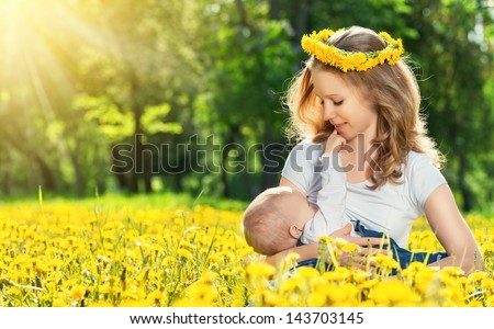 breastfeeding. mother feeding her baby in nature green meadow with yellow flowers - stock photo